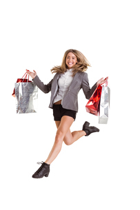 Stylish blonde jumping with shopping bagsの写真素材 [FYI02879282]