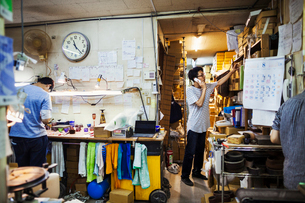 Two people at work in a glass maker's workshop and office, one on the phone.の写真素材 [FYI02880505]
