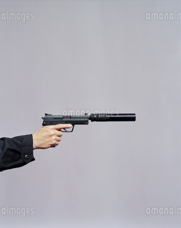 Detail of man aiming high powered hand gun with silencerの写真素材 [FYI02880512]