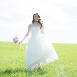草原でブーケを持ち微笑む花嫁の写真素材 [FYI02887363]