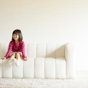 ソファーに座り微笑む女の子の写真素材 [FYI02887364]