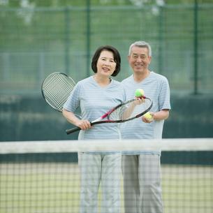 テニスラケットを持ち微笑むシニア夫婦の写真素材 [FYI02889606]