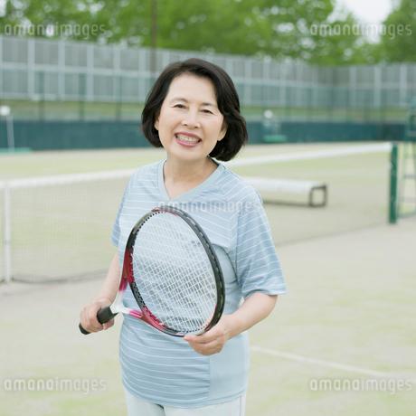 テニスラケットを持ち微笑むシニア女性の写真素材 [FYI02889795]