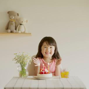 テーブルの上のケーキと微笑む女の子の写真素材 [FYI02889797]