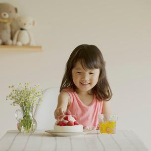 ケーキのイチゴを取ろうとする女の子の写真素材 [FYI02889804]