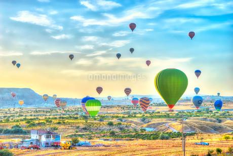 カッパドキア 朝焼けと舞い降りる気球 トルコの写真素材 [FYI02905917]