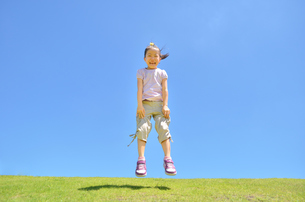 青空でジャンプする女の子の写真素材 [FYI02908536]