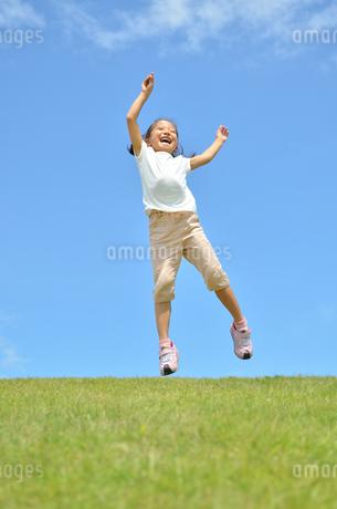 青空でジャンプする女の子の写真素材 [FYI02908537]