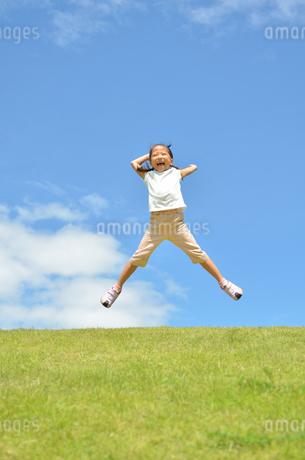 青空でジャンプする女の子の写真素材 [FYI02908538]
