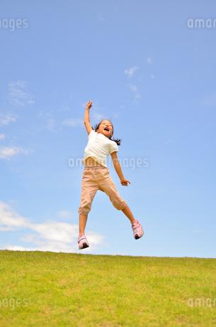 青空でジャンプする女の子の写真素材 [FYI02908539]