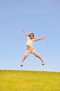 青空でジャンプする女の子の写真素材 [FYI02908540]