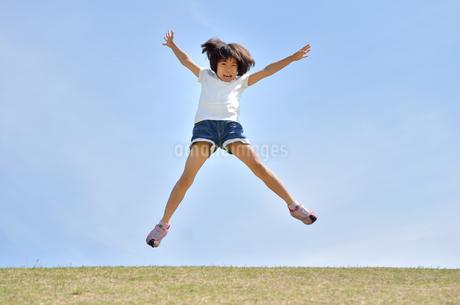 青空でジャンプする女の子の写真素材 [FYI02908541]