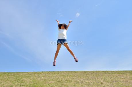 青空でジャンプする女の子の写真素材 [FYI02908542]
