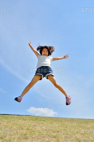 青空でジャンプする女の子の写真素材 [FYI02908543]