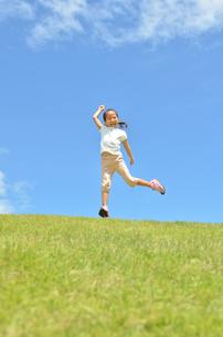 青空でジャンプする女の子の写真素材 [FYI02908544]