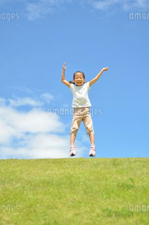青空でジャンプする女の子の写真素材 [FYI02908545]
