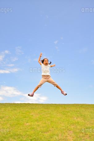 青空でジャンプする女の子の写真素材 [FYI02908546]