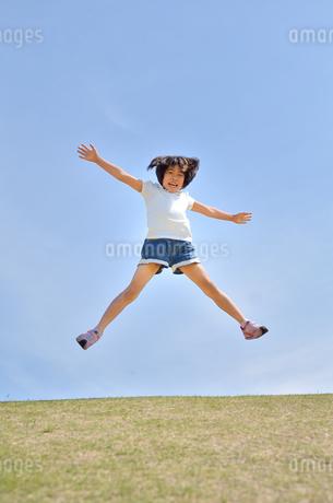 青空でジャンプする女の子の写真素材 [FYI02908547]