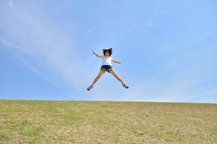 青空でジャンプする女の子の写真素材 [FYI02908548]