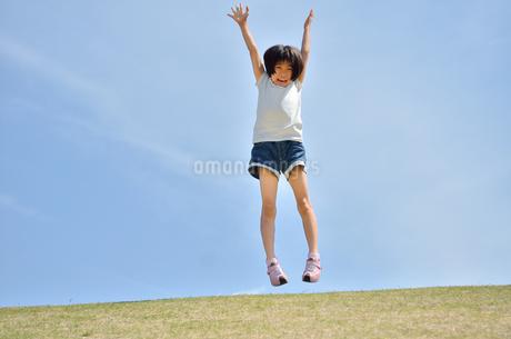 青空でジャンプする女の子の写真素材 [FYI02908549]