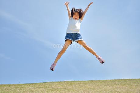 青空でジャンプする女の子の写真素材 [FYI02908550]