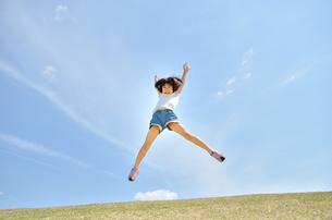 青空でジャンプする女の子の写真素材 [FYI02908551]