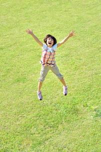 芝生広場でジャンプする女の子の写真素材 [FYI02908552]