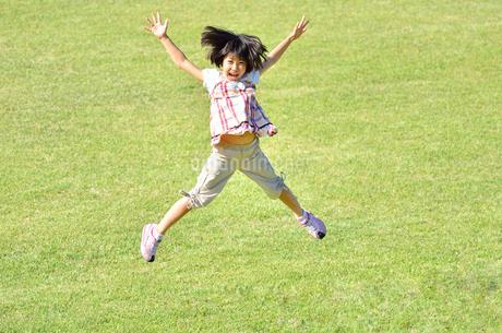 芝生広場でジャンプする女の子の写真素材 [FYI02908553]