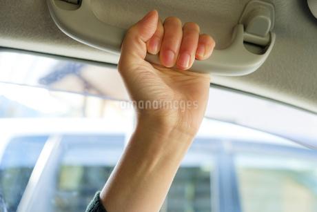 助手席のグリップを握る女性の手の写真素材 [FYI02910710]