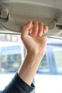 助手席のグリップを握る女性の手の写真素材 [FYI02910712]