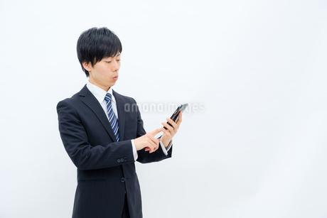 スマホを操作するビジネスマンの写真素材 [FYI02910747]