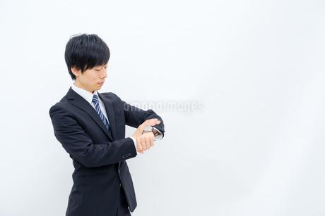 腕時計を確認するビジネスマンの写真素材 [FYI02910768]