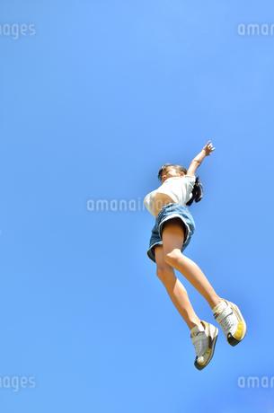 青空でジャンプする女の子の写真素材 [FYI02912906]