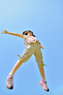 青空でジャンプする女の子の写真素材 [FYI02912907]