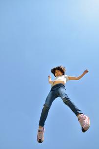 青空でジャンプする女の子の写真素材 [FYI02912908]