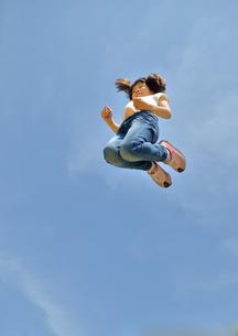青空でジャンプする女の子の写真素材 [FYI02912909]