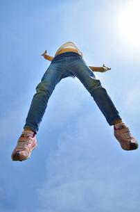 青空でジャンプする女の子の写真素材 [FYI02912910]
