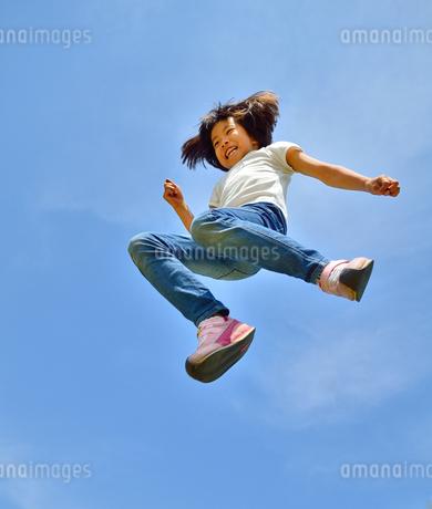 青空でジャンプする女の子の写真素材 [FYI02912911]