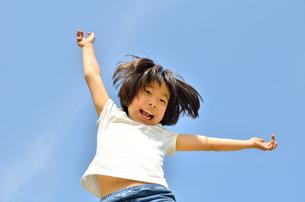 青空でジャンプする女の子の写真素材 [FYI02912912]
