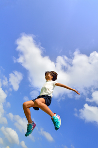 青空でジャンプする女の子の写真素材 [FYI02912913]