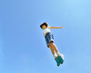 青空でジャンプする女の子の写真素材 [FYI02912914]