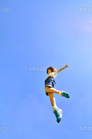 青空でジャンプする女の子の写真素材 [FYI02912915]
