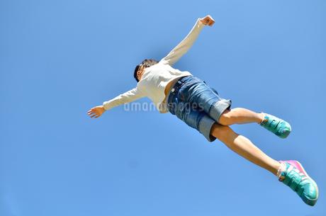 青空でジャンプする女の子の写真素材 [FYI02912916]