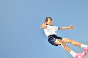 青空でジャンプする女の子(運動会、体操服)の写真素材 [FYI02912917]