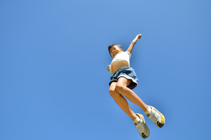 青空でジャンプする女の子の写真素材 [FYI02912918]