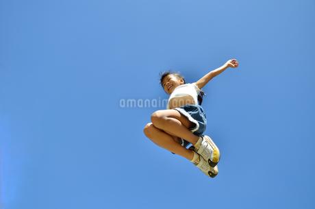 青空でジャンプする女の子の写真素材 [FYI02912919]
