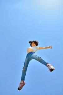 青空でジャンプする女の子の写真素材 [FYI02912920]