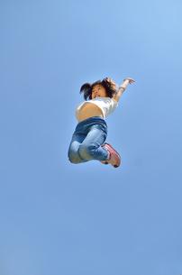 青空でジャンプする女の子の写真素材 [FYI02912921]