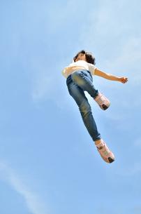 青空でジャンプする女の子の写真素材 [FYI02912922]