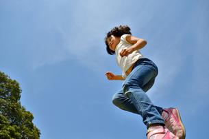 青空でジャンプする女の子の写真素材 [FYI02912923]